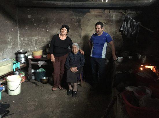 three people posing for photo in dark room