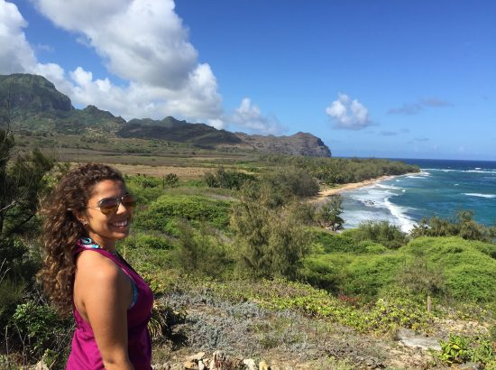 Briana Kleiner smiling in front of a beach in Kauai