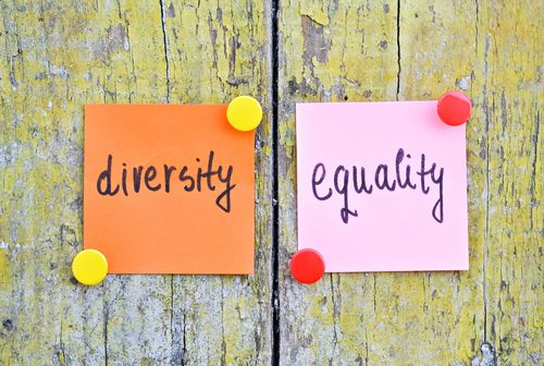 Post-it Note type stickers with handwritten words Diversity and Equality on wooden background