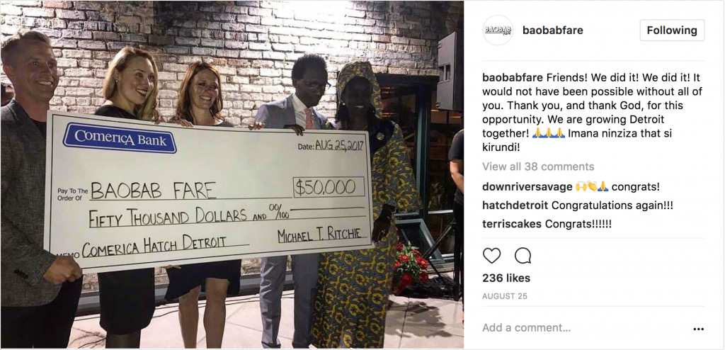 Instagram post of man holding 5 people holding large cardboard check