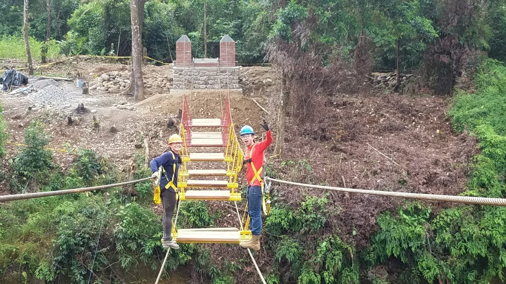 Two young adults working on the construction of a bridge.
