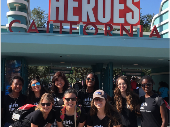 "Student's wearing ""Girls Inc"" shirts standing in front of a sign that says, ""Summer of Heroes California"""