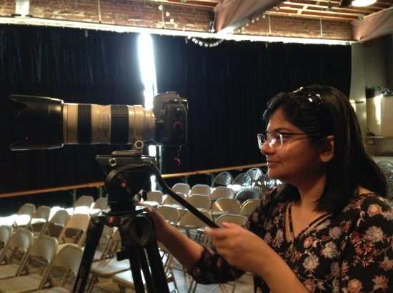 young woman looking into the back of a video camera