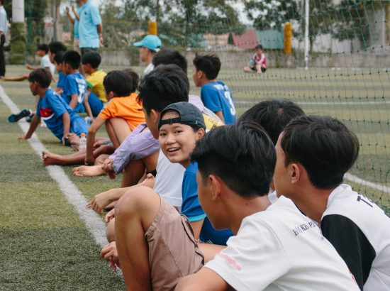 many children sitting on sidelines of soccer game