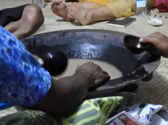 People scooping out water of a large bowl
