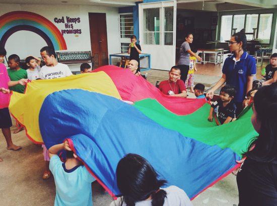 Children and staff hold rainbow parachute