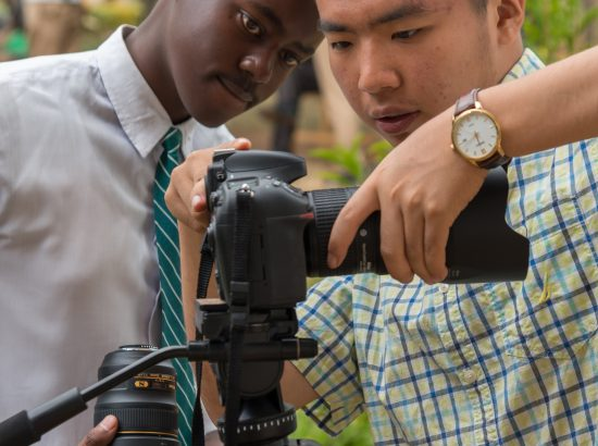 Two young adults adjusting a camera on tripod.