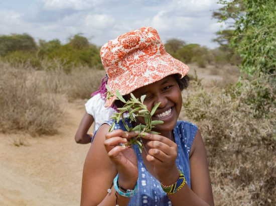 A girl wearing hat in center of photo holding leaf up to her eye.