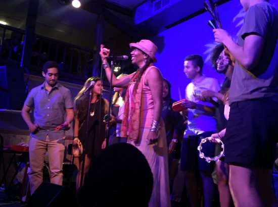 A woman at a microphone with young adults holding instruments behind her