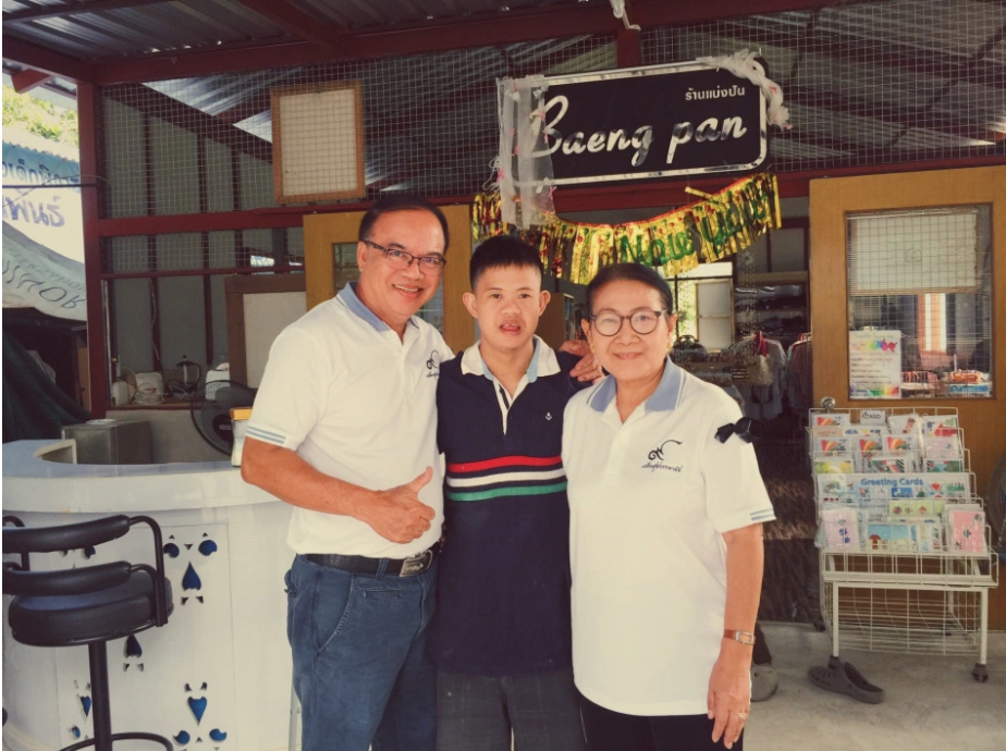Young man smiling with an older man and woman