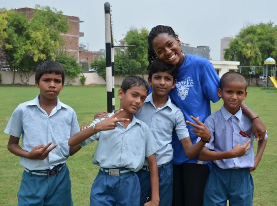 Student smiling with children