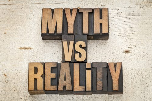 myth versus reality - concept in vintage letterpress wood type on a grunge painted barn wood background