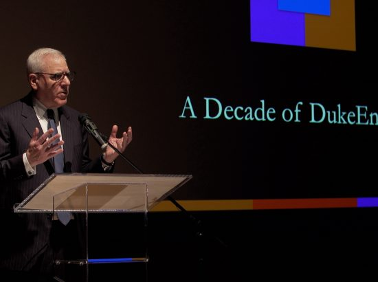 "Man stands at podium, speaking into microphone and standing in front of words ""A Decade of DukeEngage"" on a large screen."