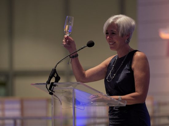 Woman standing at podium with microphone holds up champagne glass.