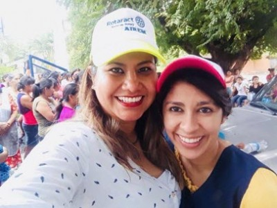 two women wearing baseball caps smiling at camera