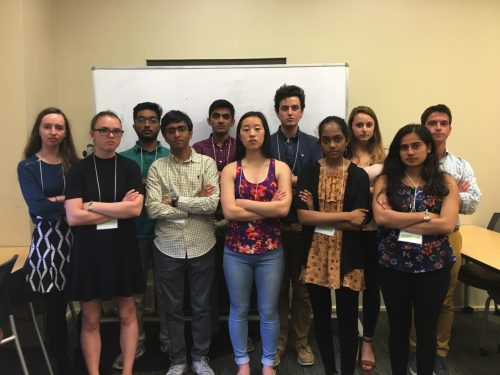 posed group, standing with arms crossed looking at camera in classroom