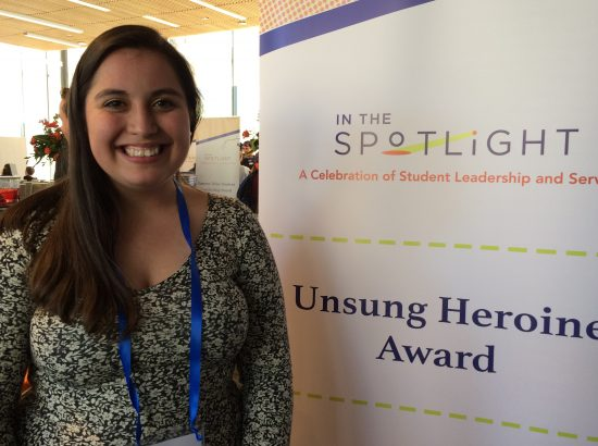young woman in a dress poses beside banner with text that reads Unsung Heroine Award