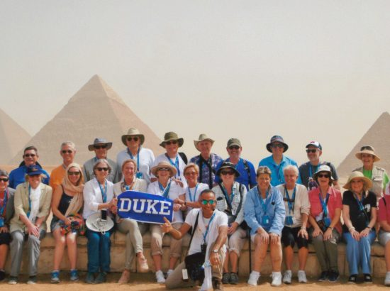 Group of people posing for photo in front of pyramids in the desert