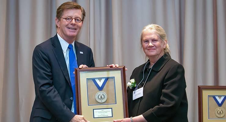 Man and woman holding framed award, smiling at camera
