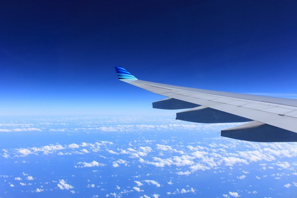 wing of airplane flying, blue sky and clouds in background