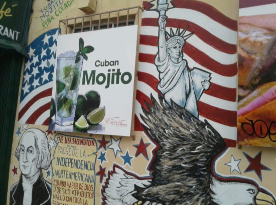 A mural of traditional American symbols like the Statue of Liberty and a bald eagle are juxtaposed by a large sign advertising Cuban mojitos.