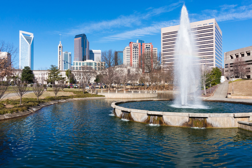 photo of city skyline during daytime under blue skies, with water fountain and lake in the foreground
