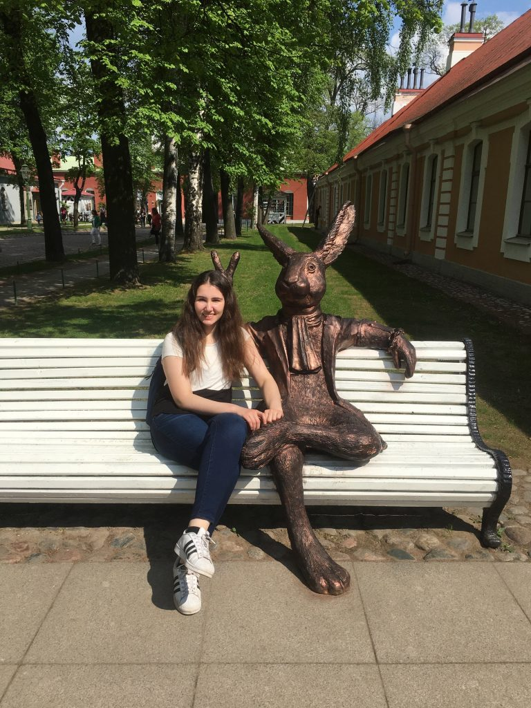 girl posing with statue