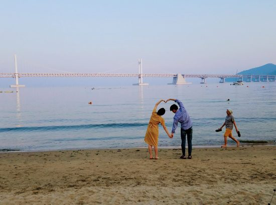 view of a beach and a bridge with a couple making a heart with their arms