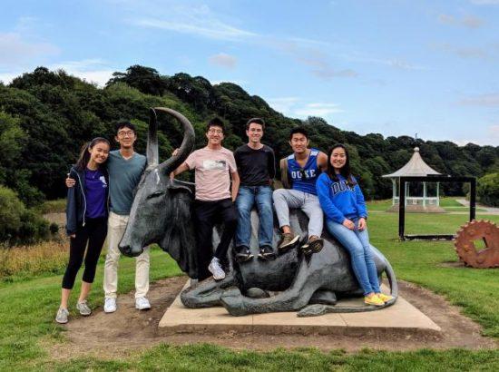 people posing next to animal statue\