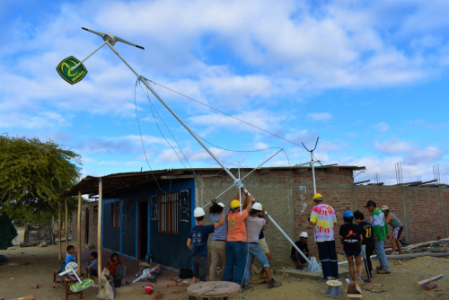 A group of people raising a wind turbine.