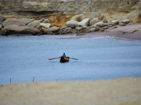 Fisherman on boat surrounded by cliffs.