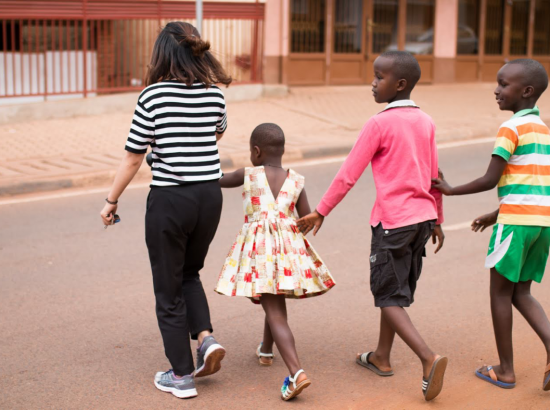 Student and three children crossing a street.