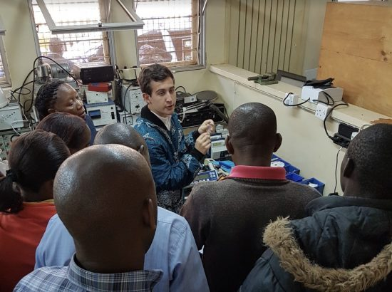 Duke student working with Tanzanians on some medical equipment