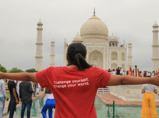 Student in DukeEngage shirt in front of Taj Mahal.