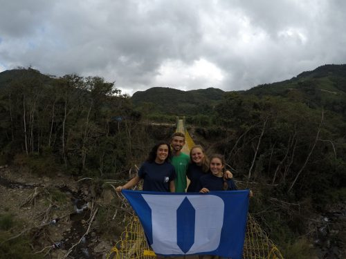 Four people standing on a bridge holding a Duke flag.