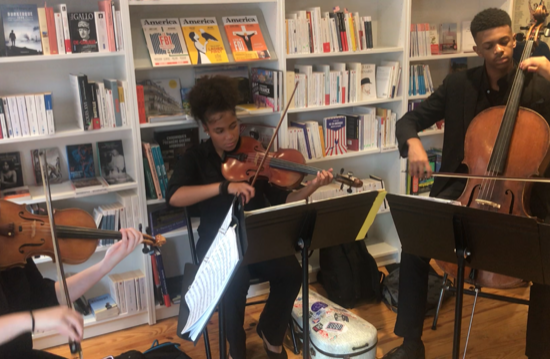 Two high school students playing the violin and one playing the cello.