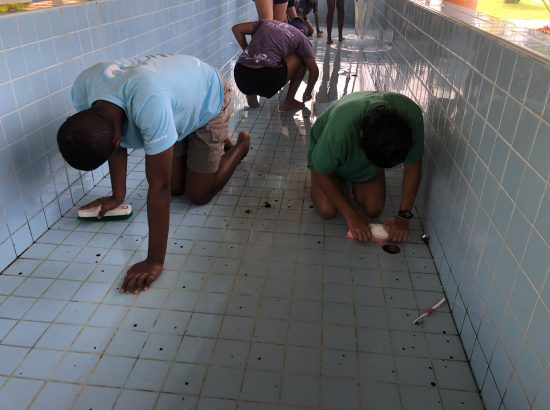 three people scrubbing a tile floor with brushes