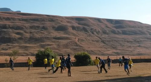 people playing soccer in a field in front of the Drakensberg mountains