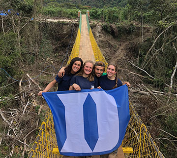 Four students with a Duke flag standing on a bridge in Bolivia.